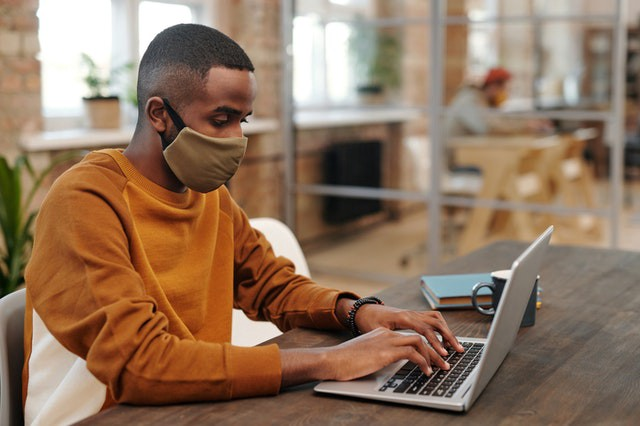 Man with laptop and facemask