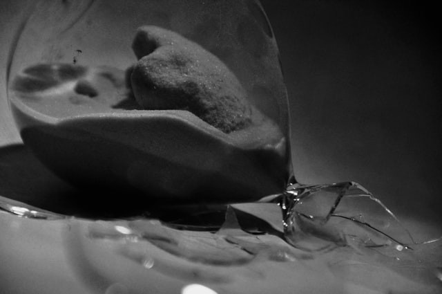 Black-and-white photo of a broken hourglass