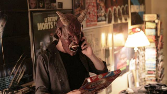 A man in a monster mask is on the phone while holding a pizza box.