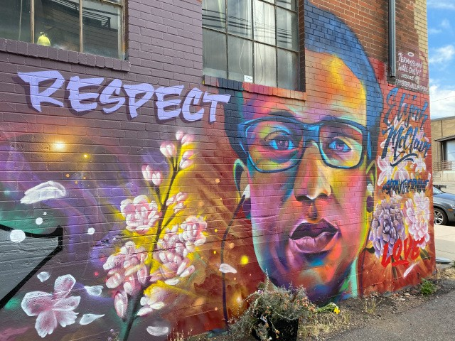A colorful mural of Elijah McClain by #SprayHisName with the word RESPECT and flowers.
