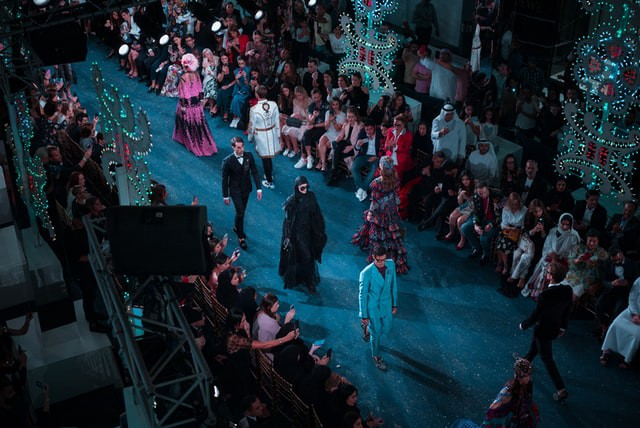 Models of varied genders in various different outfits walking on a blue carpeted runway surrounded by onlookers
