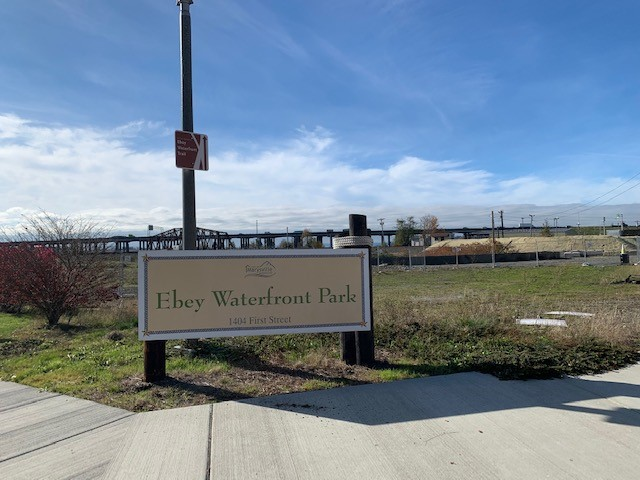 Photo of the sign for Ebey Waterfront Park, with the park in the background and bridge in the distance