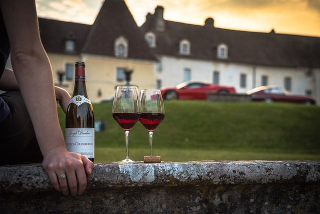 bottle of wine and two glassed of wine on ledge in front of beautiful house