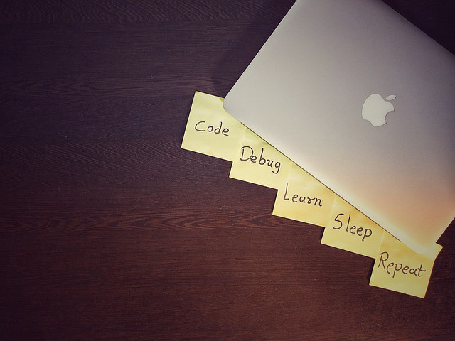 """Macbook with post it notes stating phrases, """"code, debug, learn, sleep, repeat"""""""