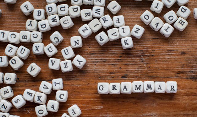 a bunch of letters on dice spelling out the word grammar