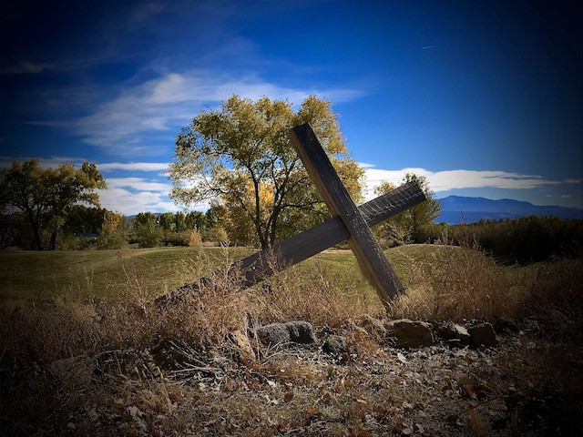 wooden cross laying sideways in a field with grass and trees in background