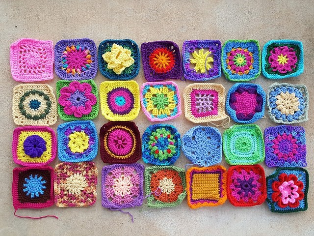 Twenty-eight granny squares in formerly assorted sizes rehabbed into six-inch crochet squares