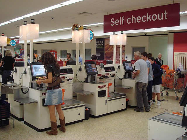 Three self-checkout machines at a store with a woman purchasing something at the first one and a man and son at the 3rd one