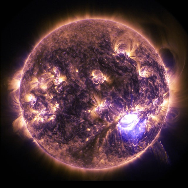 A purple orb lit up with golden light coming through it opened up spots. It looks like a planet or a ball of energy full of heat and glowing.