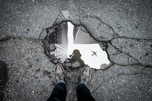 Photo Credit: Unsplash photo by Mark-Olivier Jodoin. This is a black and white photo of a buildings, airplance, and photographer in water on a cracked black top road.