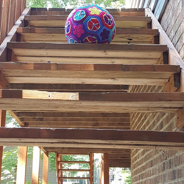 The crochet peace sign soccer ball on the stairs.