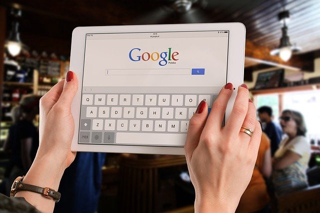 Woman holding a tablet that displays the Google homepage.