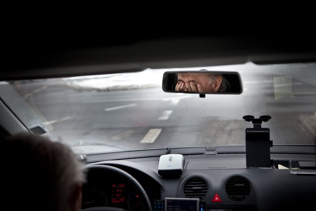 The driver of the car can be seen through the rear view mirror with his hands covering his eyes in obvious concern.
