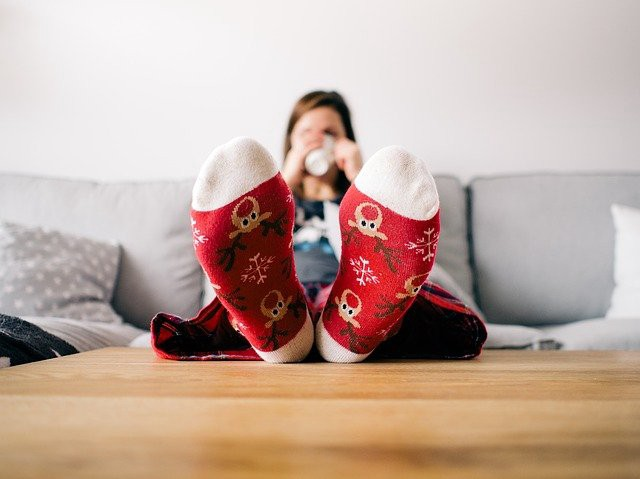 Christmas socked feet on coffee table in foreground. White woman drinking a hot beverage on couch is blurry in the background
