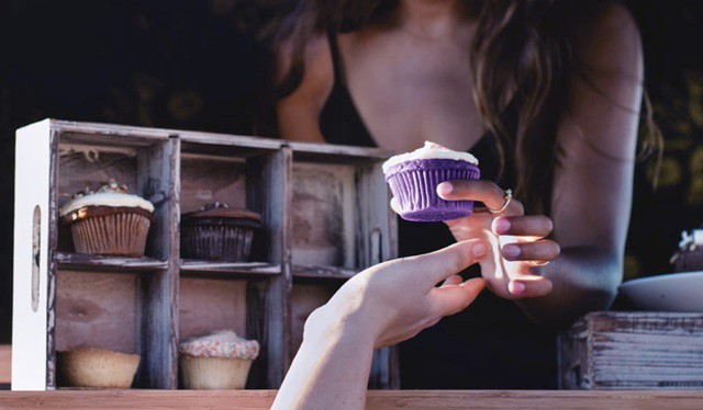 Women offering a purple cupcake to a customer