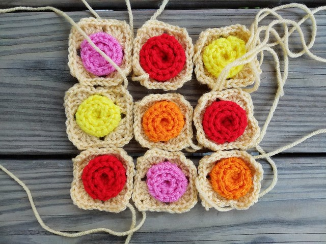 Crochet squares with crochet roses at the center made into a larger, nine patch crochet square