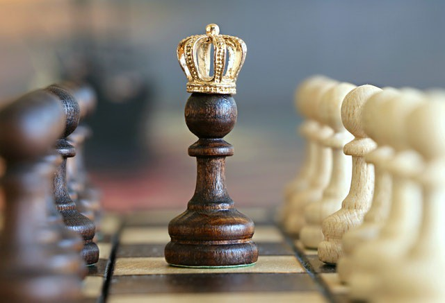 Chess board with a pawn in the center with a crown.
