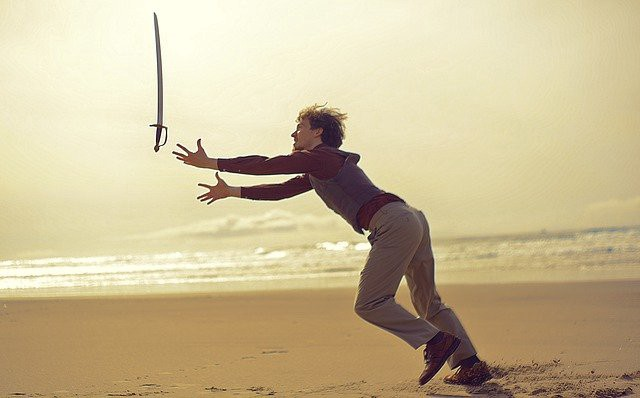 Man catching sword falling out of the sky on a beach