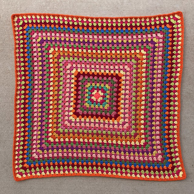 A thirty-six round multicolor crochet granny square blanket