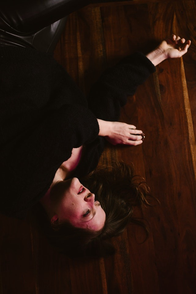 Photo Description: A woman dressed in black is laying on the floor with a look of life is absolutely over. She has reached her limits. Her wedding ring is off her finger laying on the floor next to her.