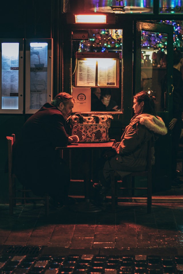 Photo Description: An older couple sit together in a dark diner having a discussion. They both look unhappy and still have their coats on. No food is on the table.