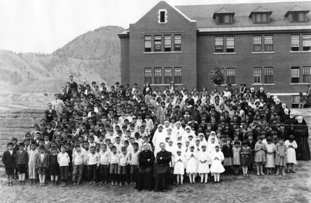 A black and white photo of children, priests and nuns in front of a residential school