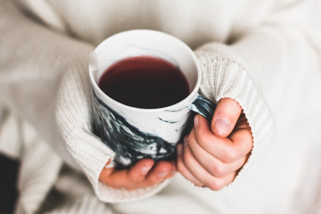 Photo of two hands holding a mug full of tea. The hands are partially obscured by the sleeves of a long, white sweater, exposing only the fingers. One hand is gripping the handle of the mug, while the other is cupped around the bottom of the mug.