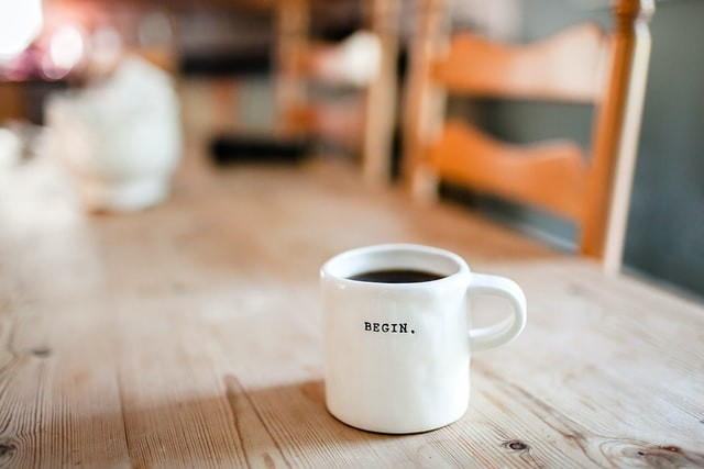 A white coffee mug sits isolated on the table. The coffee nearly reaches the top. One word is on the front in bold black letters. BEGIN.