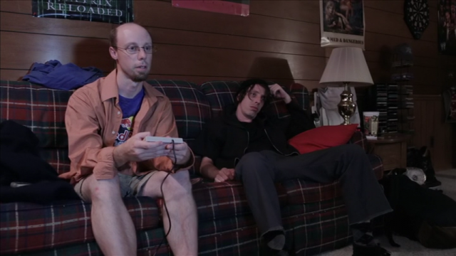Two men sit on an old couch, one plays video games.