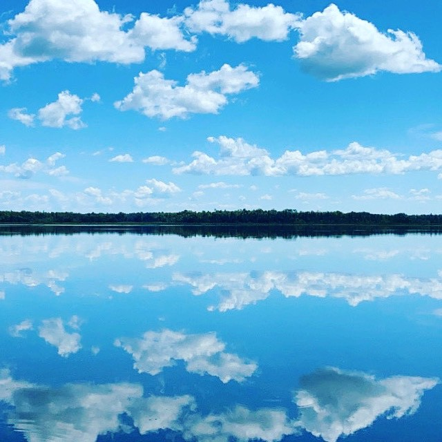 Bright blue sky filled with puffy clouds, mirrored by a still-water lake