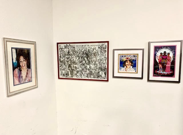 4 images of Black transgender people and art dispalyed in frames hung on a white wall.
