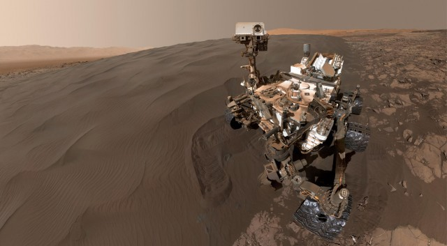 The Curiosity rover on the reddish surface of Mars.
