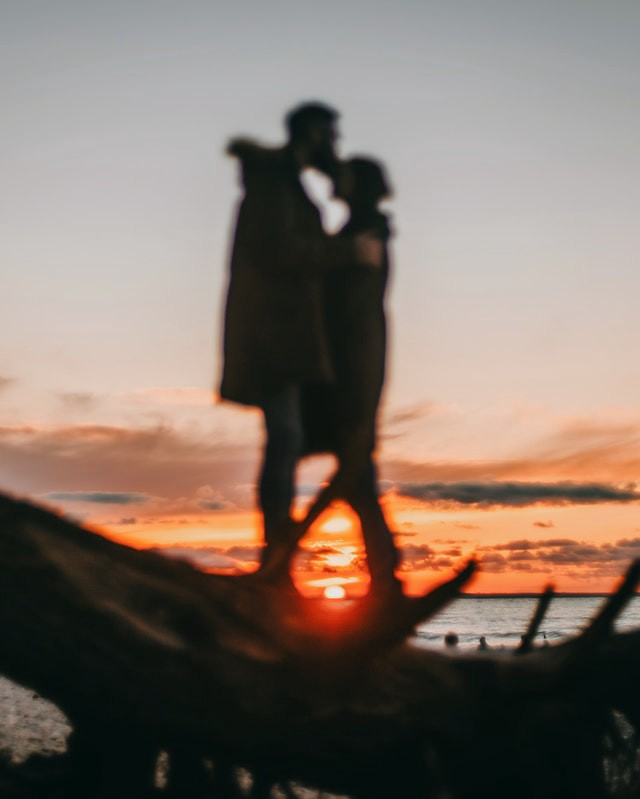 A silhouette of a pair of people embracing on a beach the view is from the ground up. The sun is setting in the background over a body of water. Twigs lie in the foreground.