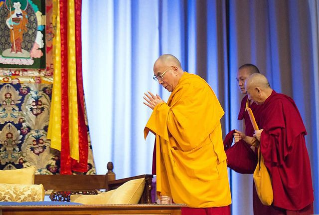 Photo of the Dalai Lama in yellow robe with other lamas in crimson robes.