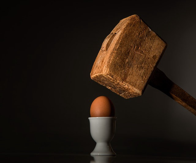 A wooden mallet is coming down atop an egg in a cup.
