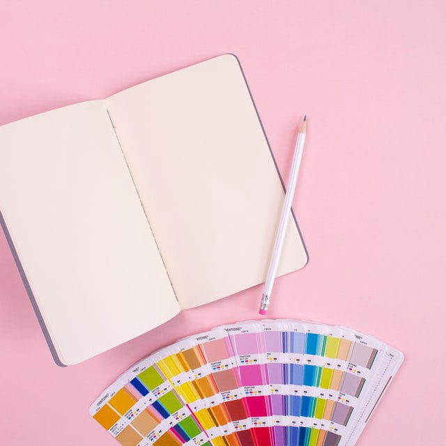 An open notebook and a pencil on a pastel pink background with a Pantone chip fan laid out below