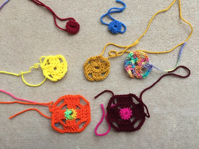 Nine future flamboyant crochet granny squares in various states of completion