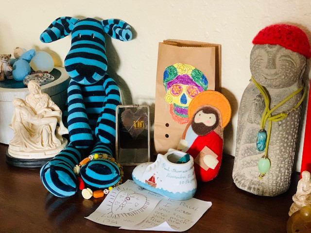 A Pietá figurine, striped dog plushie, letter from a child, and other personal items.