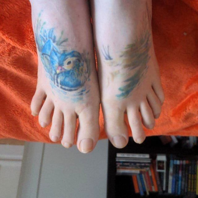 Photo of a pair of white feet on an orange blanket. The left foot has a tattoo of a Mandarin duck among some reeds, mostly done in blue. The right foot has a tattoo of a lake and more reeds. There is a bookcase full of books in the background.