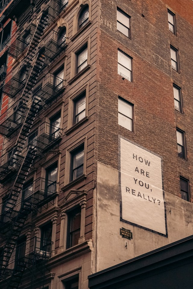 Apartment building with painted words on the side 'How are you, really?'