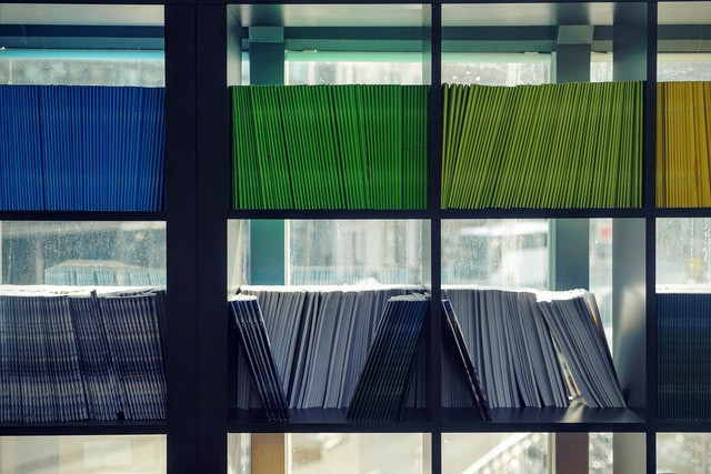 A number of notebooks neatly organized by color.