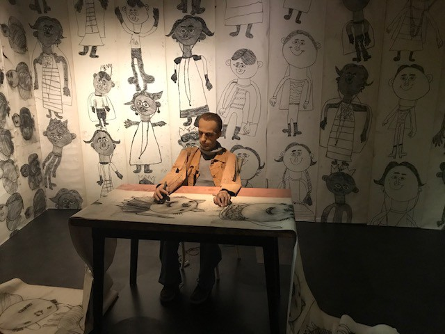 Setting with mannequin man obsessively drawing child-like drawings of children and surround by walls covered with them.