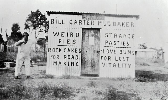 "An old photograph of a man standing next to the side of a shed, on which is painted the words: ""Bill Carter Mug Baker"""