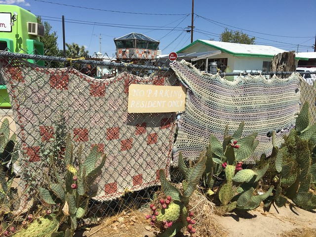 The parking lot of the World Famous Crochet Museum with sun bleached crochet afghans on the fence