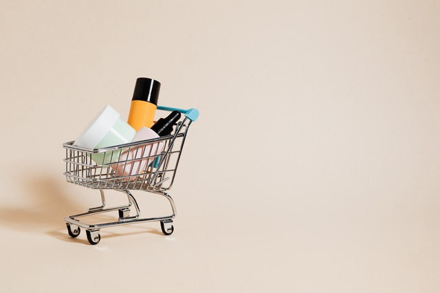 An Small/mini shopping cart with make up products.