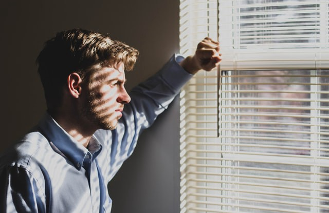 a person who is frustrated standing near a window looking outside