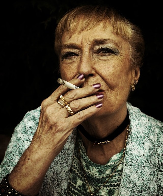 Woman with wrinkles and rings smoking cigarette.