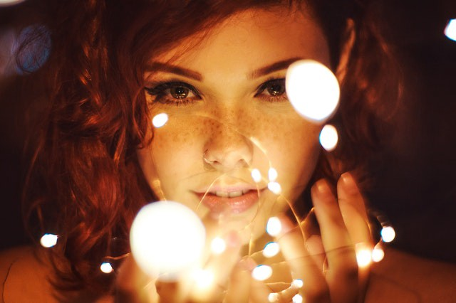 A red headed female with freckles across their skin stars into the camera with their hands cradled underneath their face while glowing orbs float in front of their face.