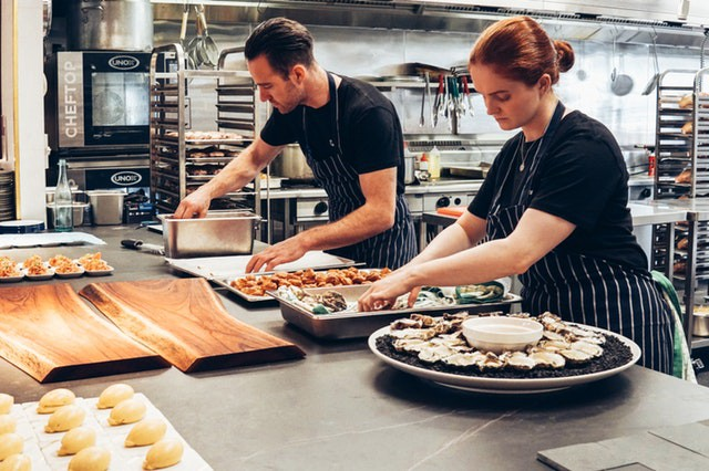 Cooks creating platters in the kitchen. More productive to work together.