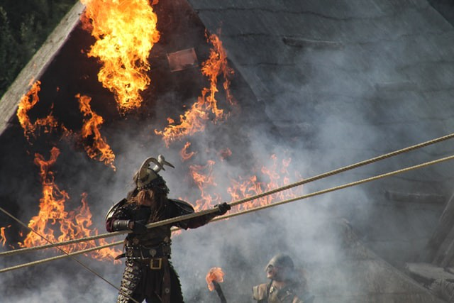 Viking pulling rope in front of building engulfed with flames